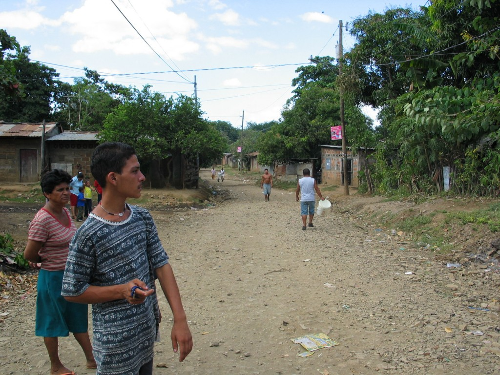 Maria Elena and her son in the street in front of their house. The purple posters are Sandinista advertisement.
