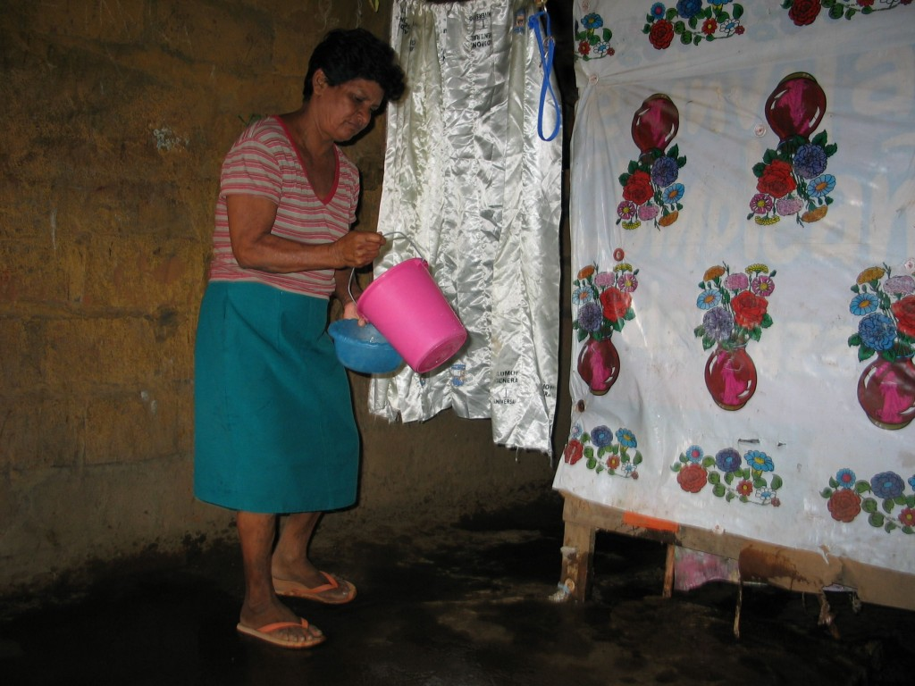 Maria Elena cleans the dirt floor inside her shed by dropping water on it.
